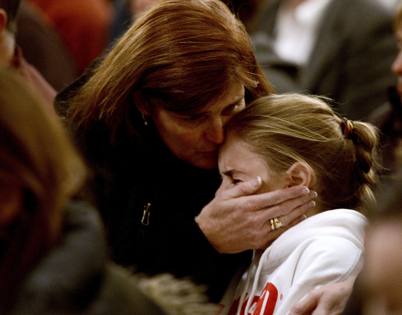 "A woman comforts a young girl during a vigil service last week in Newtown, Conn., for victims of the Sandy Hook Elementary shooting. Programs for children with mental and neurological disorders help students adjust to the world around them, but ""once they have finished public school, all assistance ends,"" isolating at-risk young men, a reader says."