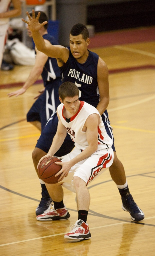Kevin Manning of Scarborough looks for an open teammate while guarded by Portland center Matt Talbot. Manning led Scarborough with 19 points, while Talbot finished with 14 points for the Bulldogs.