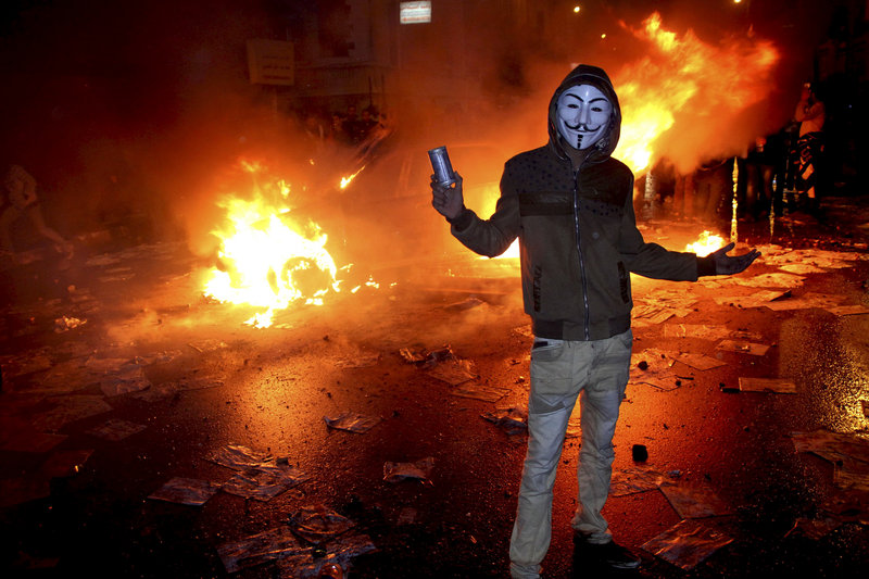 A masked protester poses with a tear gas canister in front of a burning vehicle during clashes between opponents of Egyptian President Mohammed Morsi and his Islamist supporters in Alexandria, Egypt, on Friday.