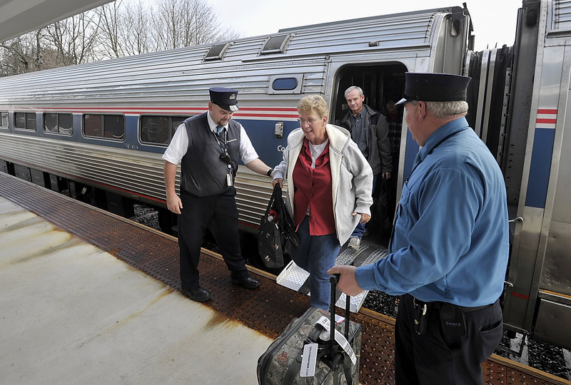 Downeaster conductor Chuck Moyer, left, helps passenger, Jean Townsend, who lives in Naples Fla., as she leaves the train in Freeport. Press Herald file photo