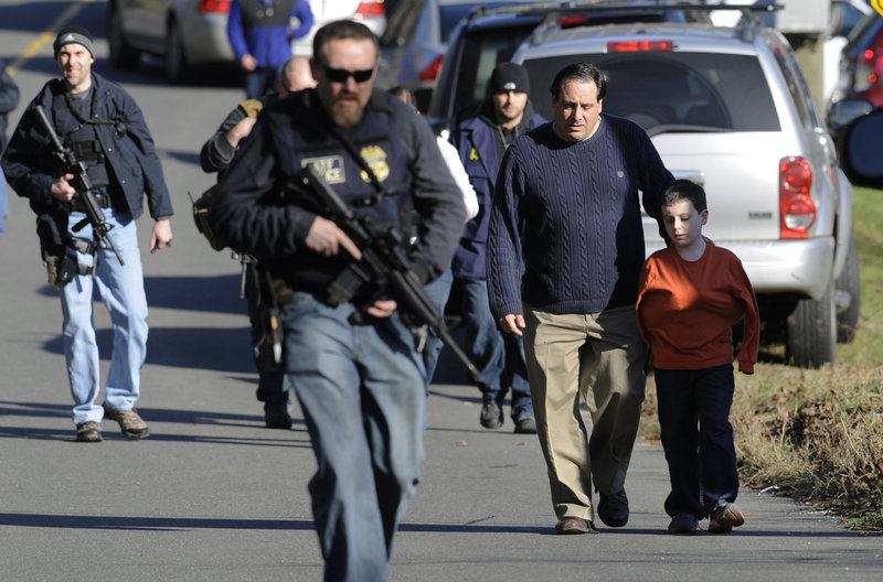 Parents leave a staging area after being reunited with their children Dec. 14 at Sandy Hook Elementary School in Newtown, Conn., where Adam Lanza fatally shot 20 children. Lanza is said to have had Asperger's disorder, but experts say that would not have predisposed him to violence.