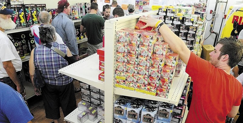 "Tyler Basinger restocks shelves as customers line up in July at the Pyro City fireworks store in Manchester. Owner Steve Marson said he plans to open two more stores in Maine next year. ""In my opinion, it was a very safe year,"" he said."