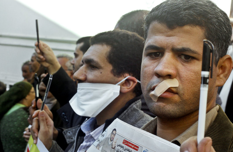 Egyptian journalists tape their mouths and raise their pens during a demonstration against the Islamist-backed constitution in Cairo on Sunday. Egypt's opposition fears that freedom of the press will be limited under the increasingly religious government.