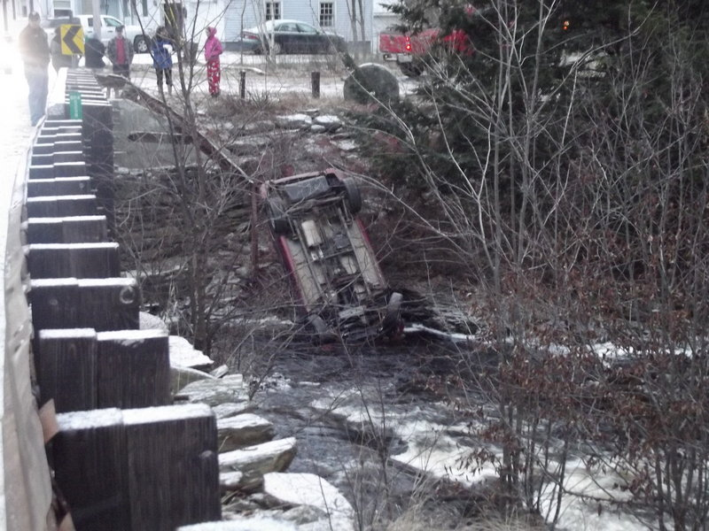 An overturned SUV lies on the riverbank off Little River Road in Lebanon Tuesday, after police say a 34-year-old Sanford woman fell asleep at the wheel. She was not seriously hurt.