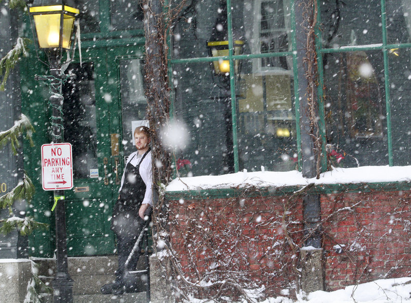 Christopher Geer, a sous chef at Vignola Cinque Terre, watches as snow falls Thursday at Dana and Wharf streets in Portland. Geer said the restaurant would be closing for the night Thursday because of the storm.