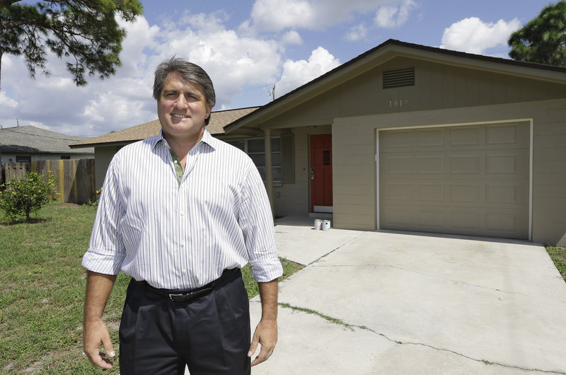 "Andrew Neitlich stands outside one of his investment homes in Venice, Fla. Neitlich once worked as a financial analyst, picking stocks for a mutual fund, but like many others he is selling his stock now. He says he prefers to invest in real estate because it's something he can ""control."""