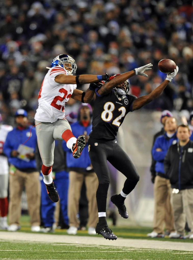 Torrey Smith of the Baltimore Ravens makes a one-handed catch despite the efforts of the New York Giants' Corey Webster in last Sunday's game, won by the Ravens.