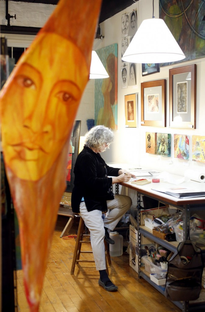 "Visual artist Nora Tyron works on a drawing in her studio in the North Dam Mill during the ArtWalk. In the foreground is a piece from a series titled ""The Family Tree"" created from wood, canvas, stone, and acrylic paint."