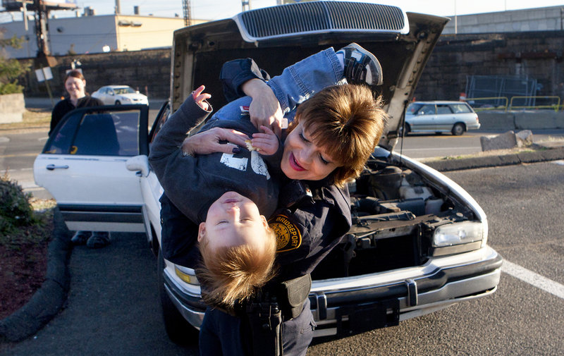 Amanda Arnold watches as Bridgeport Police Sgt. Melody Pribesh plays with her 19-month-old son, Kason, after getting her car fixed in Bridgeport, Conn. Officers fixed Arnold's car after it broke down late at night while she was traveling to Florida.