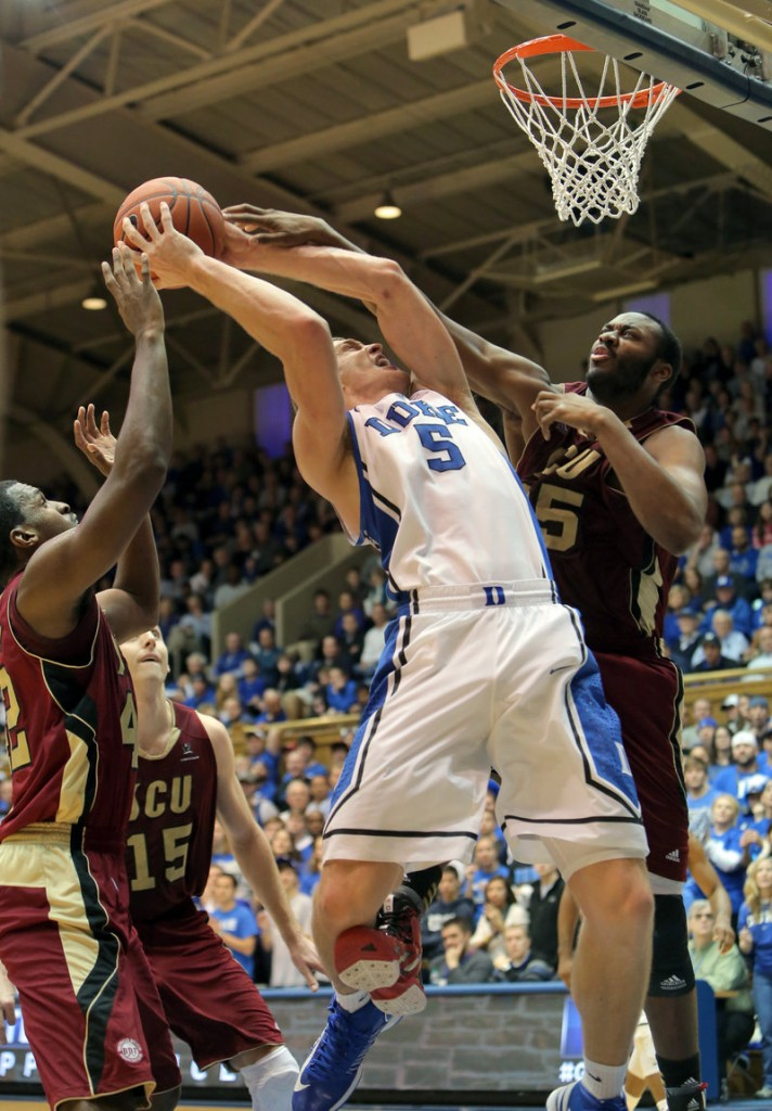Duke's Mason Plumlee, center, is fouled on a drive by Santa Clara's Robert Garrett during the first half of Duke's 90-77 win over the Broncos on Saturday at Durham, N.C.
