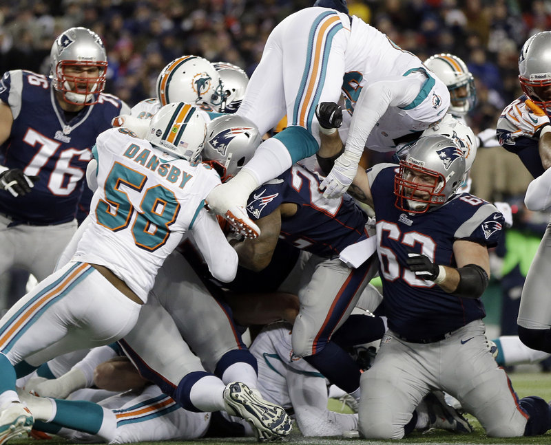 New England's Stevan Ridley, center, is surrounded by Dolphins, including linebacker Karlos Dansby (58), as he scores a touchdown in the second quarter of the Patriots' 28-0 win at home on Sunday.