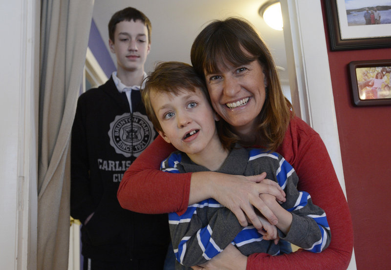 Aidan Bowie, 11, along with his mother Heather and brother Liam, 13, in the background, at their Berwick home on Monday.