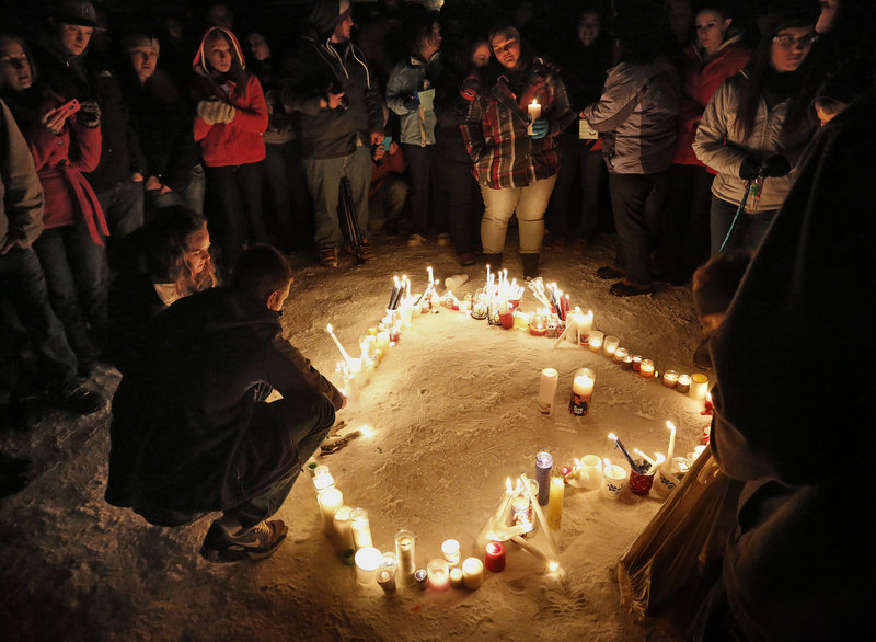 Hundreds attended a vigil at Rotary Park in Biddeford on New Year's Eve to remember Derek Thompson, 19, and his girlfriend Alivia Welch, 18, whow ere shot and killed by their landlord James Pak on Saturday. In the above photo, Friends and family form a heart with their candles.
