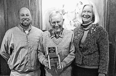 Longtime Pine Tree Society Kids' Project volunteer Tom Morgan, center, receives a special plaque at his recent retirement party. With him are Pine Tree's volunteer coordinator Jeremy Lucas, left, and Executive Director Anne Marsh.