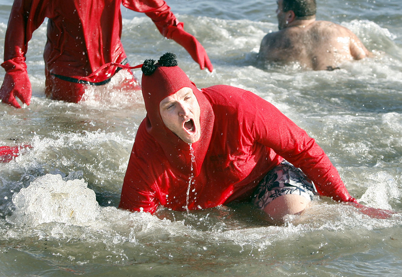 "Dave Roberts of Washington, D.C., and a member of team ""I Dip, You Dip, We Dip"" falls into the ocean on his third dip during the 25th annual Lobster Dip to benefit Special Olympics Maine in front of The Brunswick in Old Orchard Beach on Tuesday."