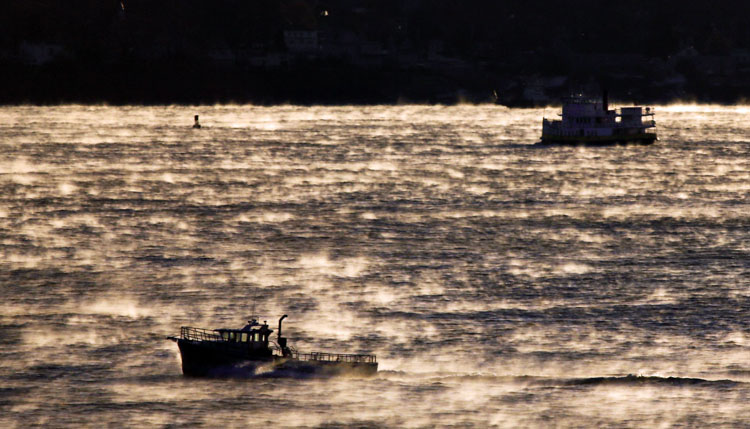 Arctic sea smoke, created when very cold air touches warmer water, surrounds boats as they head out into Casco Bay just before sunrise Wednesday morning.
