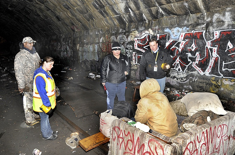 John Patriquin/Staff Photographer: Maine HUD field director Bill Burney, Angela Havlin, Alicia Martinez and Josh O'Brien all with the Oxford Street Shelter interview a homeless man in the tunnel under the Casco Bay Bridge as the city of Portland conducted its annual homeless point in time survey, Wednesday January 30,2013.