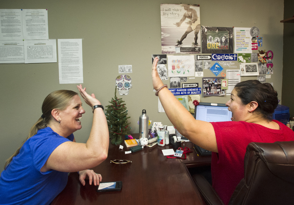 Lisa Donlea, left, and Susan Roberts, a certified enrollment officer, celebrate after working on Donlea's federal health insurance exchange enrollment online in Laguna Beach, Calif., last week. Jan. 1 marks the start date for one of the centerpieces of the Affordable Care Act: insurance plans offered by private companies through either federal or state-run marketplaces, or exchanges.