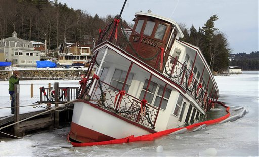 Owner of the MV Kearsarge, Peter Fenton, left, examines his sinking dinner cruise ship in Sunapee Harbor Friday, Jan. 11, 2013 in Sunapee, N.H. Authorities said the ship started to go under at about 7:45 p.m. Thursday, and part of the lower deck at the back of the boat was under water Friday morning. It was not immediately known what caused the problem. The MV Kearsarge has been taking visitors around Lake Sunapee from May through October for over 30 years. (AP Photo/Jim Cole)