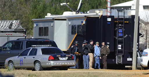 Law officers stand beside the Alabama State trooper mobile command post at the Dale County hostage scene in Midland City, Ala. on Thursday, Jan. 31, 2013. A gunman holed up in a bunker with a 6-year-old hostage has kept law officers at bay since the standoff began when he killed a school bus driver and dragged the boy away, authorities said. (AP Photo/Montgomery Advertiser, Mickey Welsh)