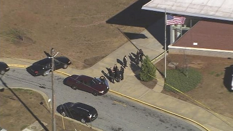 In this image made from video and released by WSB-TV, authorities investigate the scene of a school shooting, Thursday, Jan 31, 2013 in Atlanta. Authorities say a 14-year-old has been wounded in a shooting at an Atlanta middle school and a suspect has been taken into custody. Atlanta police spokesman Carlos Campos says the wounded student has been taken