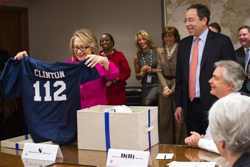 This handout photo provided by the State Department shows Secretary of State Hillary Rodham Clinton holding up a football jersey as she returned to work on Monday after a month-long absence.