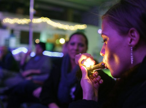 Rachel Schaefer smokes marijuana at the opening of Club 64, a marijuana social club in Denver, on Dec. 31, 2012. Maine voters approved social clubs in 2016, but lawmakers voted Wednesday to eliminate references to club licensing in their rewrite of the Marijuana Legalization Act.