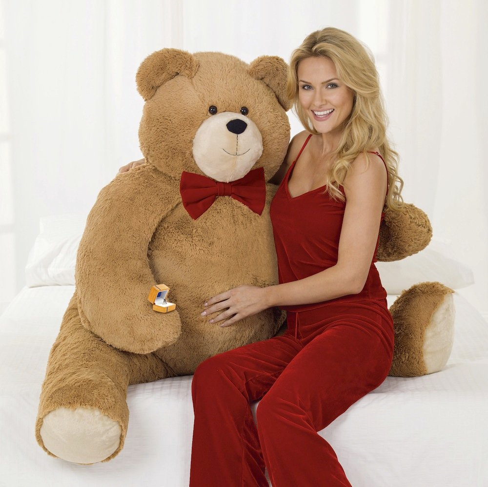 "In this photo released by Vermont Teddy Bear, a model poses with the the Big Hunka Love Diamond Bear. The Shelburne, Vt.-based company has put a $30,000 price tag on the 4½-foot-tall bear. That's because the bulk of the price is the 5.9 carat, one-of-a-kind ""fire rose"" diamond ring made by Perrywinkle's Fine Jewelry in Burlington. (AP Photo/Vermont Teddy Bear)"