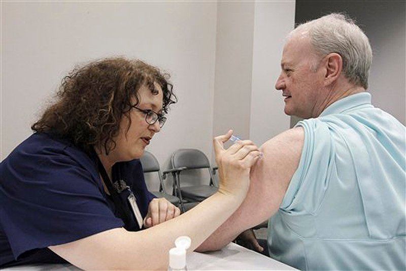 Bill Staples, a Mississippi Department of Health employee, is given a flu vaccine shot by registered nurse Rosemary Jones, also with the health department, in Jackson, Miss., last fall. A survey by Centers for Disease Control and Prevention researchers found that in 2011, more than 400 U.S. hospitals required flu vaccinations for their employees and 29 hospitals fired employees that were not vaccinated against the virus.