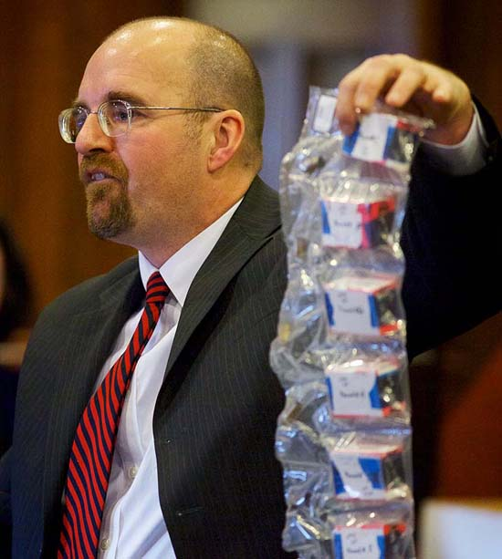 Assistant Attorney General Donald Macomber holds a bag of spent shell casings found at the scene of the crime as he presents his opening arguments in the Joel Hayden double murder trial in Cumberland County Superior Court in Portland on Monday.
