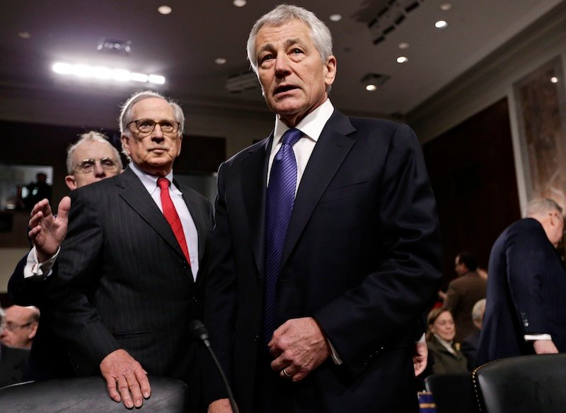 Republican Chuck Hagel, a former two-term senator and President Obama's choice to lead the Pentagon, arrives at the Senate Armed Services Committee for his confirmation hearing, on Capitol Hill in Washington, Thursday, Jan. 31, 2013. Former committee chairman, Democrat Sam Nunn, left, introduced Hagel. If confirmed, Hagel, a decorated Vietnam combat veteran, would be the first enlisted man to serve as defense secretary. (AP Photo/J. Scott Applewhite)