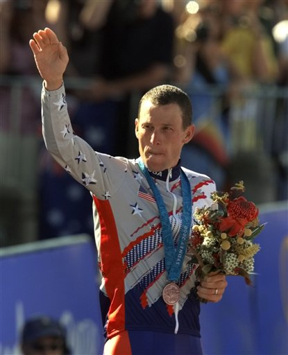 In this Sept. 30, 2000, photo, Lance Armstrong waves after receiving the bronze medal in the men's individual time trials at the 2000 Summer Olympics cycling road course in Sydney, Australia.