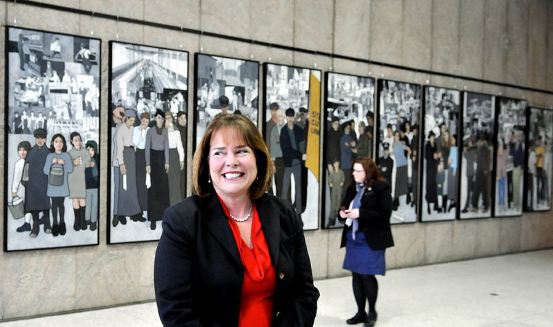 Jeanne Paquette, Maine's commissioner of labor, unveiled the labor mural on display on the wall of the Cultural Building atrium, which serves as the entryway to the Maine State Museum, in Augusta on Monday. The mural was hung over the weekend, after being removed by Gov. Paul LePage in 2011 from the Department of Labor's offices on Enterprise Drive in Augusta.