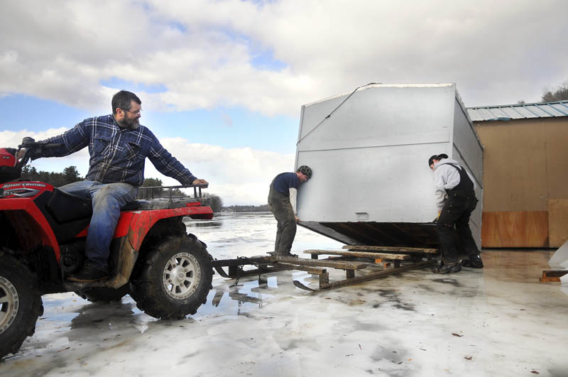 Mike Baker, left, backs under a smelt shack that Brandon Sutherburg, right, and Jeb Baker recovered Thursday on the Kennebec River in Pittston. Shacks at smelt camp operations the length of the river moved across the ice from high wind that gusted up to 50 miles-per-hour. Bakers Smelt Camps had a half dozen get blown away with one still stranded near the center of the river on thin ice, Baker said.