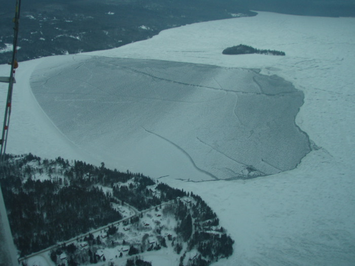 A photograph taken Friday from a Maine Warden Service aircradt of the area on Rangeley Lake, where three snowmobilers were lost on Sunday and presumed drowned. The section of lake has frozen over, further delaying search and recovery efforts, according to the warden service.