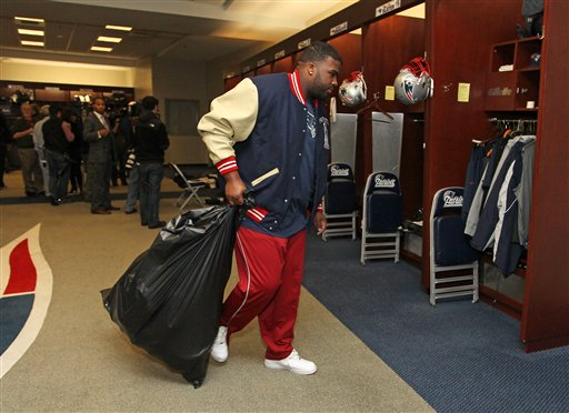 New England Patriots defensive tackle Brandon Deaderick carries a trash bag of his belongs through the locker room at Gillette Stadium in Foxborough, Mass., on Monday.