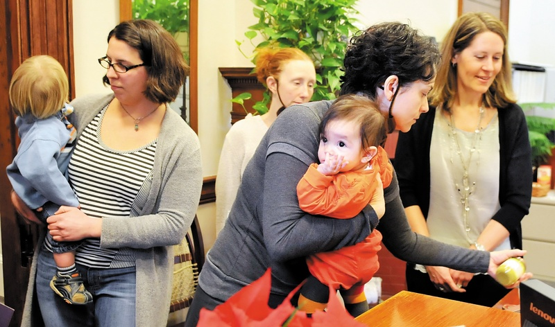 Lilijana Cvetkoska of Cape Elizabeth holds her infant daughter while leaving baby food on the desk of Gov. Paul LePage's receptionist on Jan. 9, as she and others show their support for a ban on BPA in baby food containers.