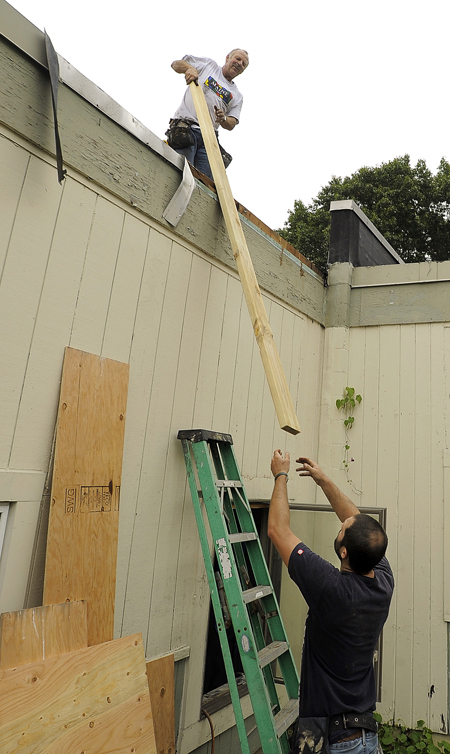 Gabe Souza/Staff Photographer: Bill Colby, left, top, of Colby Contractors in South Portland, receives a wood board from Aaron Gallagher, right, as the two work to seal the damaged roof of the Hall Elementary School before a storm blew in Tuesday, September 18, 2012, after a fire damaged the school earlier that week.