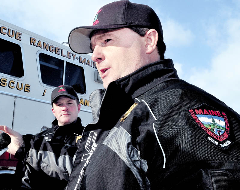 """Maine Warden Service Lt. Kevin Adam, right, comments Tuesday about the ongoing efforts to recover the bodies of three snowmobilers who went through the ice Sunday on Rangeley Lake in Rangeley. The body of a fourth victim was recovered earlier. """"I've been a game warden for 21 years. I can't think of another incident where four people went in to the same body of water in one night,"""" Adam said."""