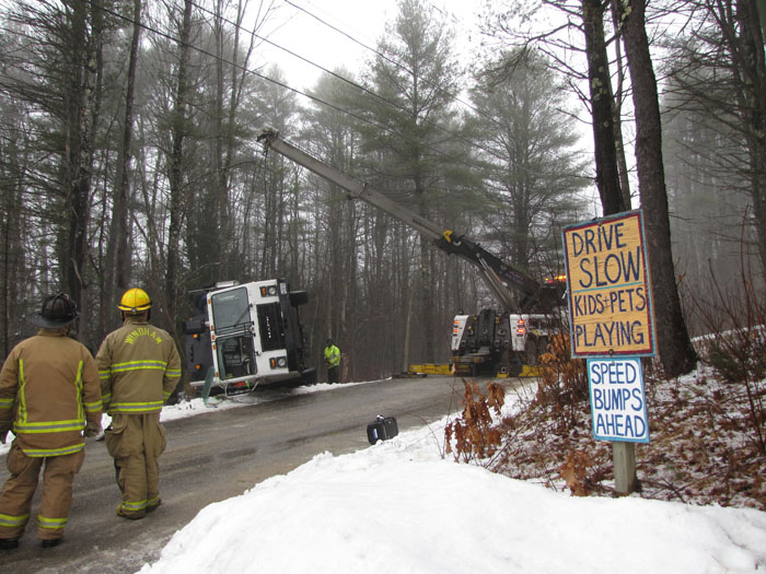 Rescue personnel watch as a tow crane begins to lift a Pine Tree Waste truck that rolled over in Windham on Wednesday morning. Contributed photo by Elizabeth Nangle.