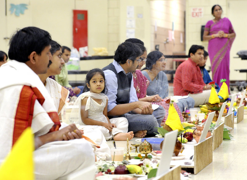 Three-year-old Srehitta Patnayakuni watches with her parents at the Dec. 1 prayer service held by the Maine Hindu Temple. The group's offer on a Westbrook church was later accepted and fundraising was successful.