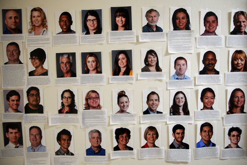 Photos of some of the newly hired reporters at the Orange County Register line the newsroom wall. About 75 new journalists have been added with more on the way.