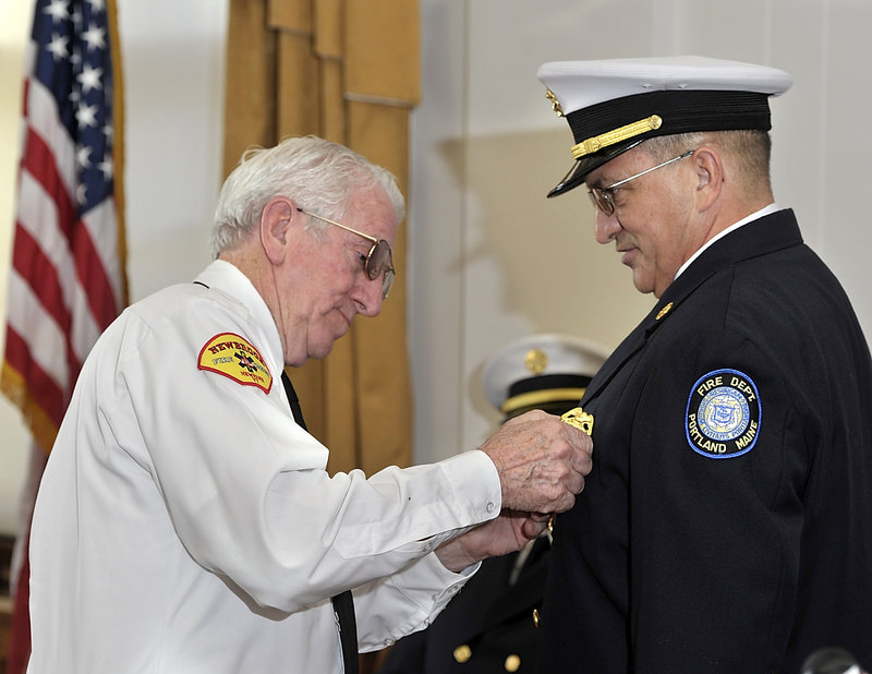 Jerome LaMoria, right, Portland's new fire chief, has his chief's badge pinned on him by his father, Norman – a former fire chief in Vermont – during the swearing-in ceremony at City Hall on Thursday.
