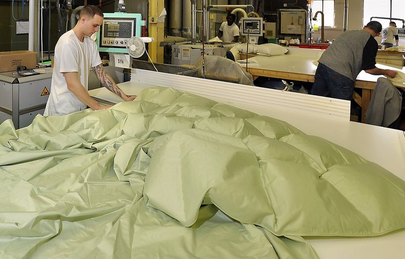 Bobby Hipsher fills a comforter with down in 2011 at the Cuddledown Inc. factory on Canco Road in Portland.