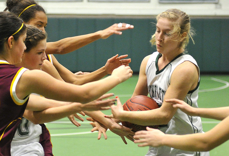 Waynflete's Martha Veroneau tries to keep the ball away from several outstretched arms.