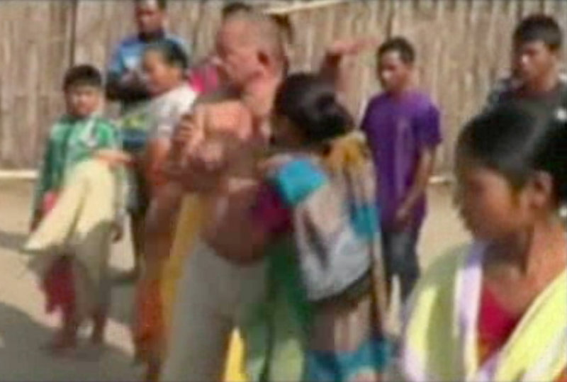 Bikram Singh Brahma, center, a leader of India's ruling Congress party, is slapped by a woman in the village of Santipur, India, on Thursday. Police said he was visiting the village when he entered a woman's house at 2 a.m. and raped her.