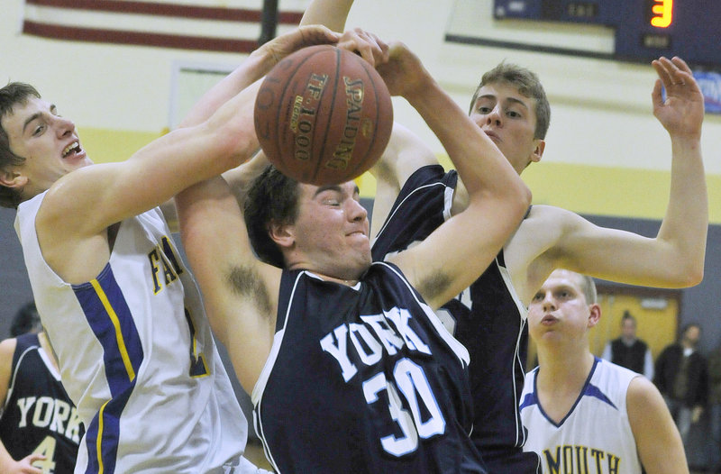Luke Claflin, right, of York battles for a rebound with Falmouth's Charlie Fay in Thursday's boys' basketball game at Falmouth. The Yachtsmen stayed unbeaten by knocking off the previously perfect Wildcats by 20 points.
