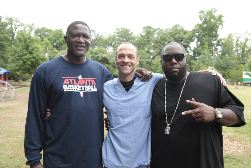 Dominique Wilkins, an NBA Hall of Famer who is considered one of the best dunkers of all times, left, Dr. Kevin Strong, founder of Dunk the Junk, and rap artist Killer Mike attend the Dunk the Junk event at the Emma Hutchinson Elementary School in Atlanta.