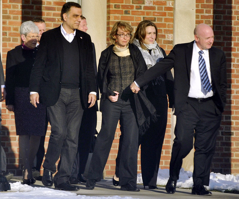 Former Rep. Gabrielle Giffords, center, with her husband Mark Kelly, at right, visits Newtown, Conn., on Friday.