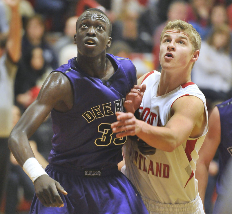 Labson Abwoch of Deering, left, and Ben Burkey of South Portland jostle for rebounding position Friday night during Deering's 58-52 victory in overtime.